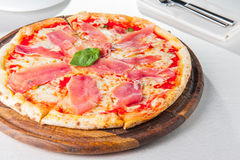 Tasty whole Italian pizza topped with thinly sliced prosciutto ham on the served restaurant table. Stock Photography