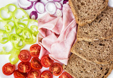 Tasty whole wheat bread with ham, onion, paprika and cherry toma Stock Photo