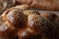 Tasty wicker bun with sesame on the board close-up royalty free stock photos