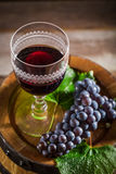 Tasty wine in glass with grapes on wooden barrel Royalty Free Stock Image