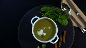 Tasty winter appetizer of thick broccoli soup. Tasty winter appetizer of thick broccoli and spinach soup served in a white bowl spinning on a carousel with fresh stock footage