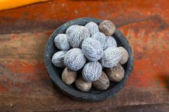 Tasty winter spice whole dried nutmeg, used as an ingredient in. Many dishes, eggnog, mulled wine, close up on old wooden table close up Royalty Free Stock Photography
