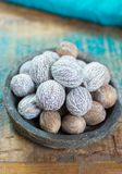 Tasty winter spice whole dried nutmeg, used as an ingredient in. Many dishes, eggnog, mulled wine, close up on old wooden table close up Royalty Free Stock Image