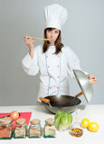 Tasty wok cooking lesson. Young chef in a neutral background tasting her cooking Royalty Free Stock Image