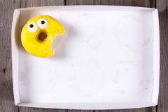Only tasty yellow bitten donut in empty white box. Only tasty yellow donut in empty white box. Top view Royalty Free Stock Image