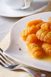 Tasty yellow pumpkin gnocchi with butter, vertical Stock Image