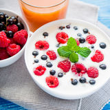 Tasty yoghurt with raspberry on wood blue table. Dessert food breakfast royalty free stock photography