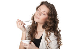 Tasty yogurt. Close-up portrait of young female enjoying taste of yogurt with closed eyes isolated on white Royalty Free Stock Photos