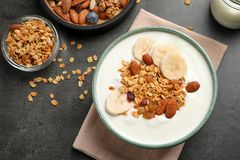 Tasty yogurt with banana and granola for breakfast. On table, top view stock photography