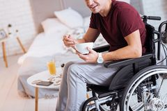 Positive delighted disabled man while eating. It is tasty. Young male person sitting on his wheelchair and holding white plate while keeping smile on face Royalty Free Stock Photo