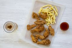 Tasy fast food: fried chicken drumsticks, spicy wings, French fries and chicken strips with sour-sweet sauce and cold beer over wh. Ite wooden background, top royalty free stock photos