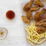Tasy snabbmat: stekt kycklingtrumpinnar, kryddiga vingar, pommes frites och fega remsor med sur-sötsak sås och kallt öl över arkivfoton