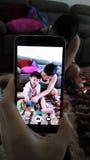 Tata bawić się zabawki z dziećmi chapał z handphone Zdjęcie Royalty Free