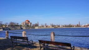 The tata castle with benches from the lake in the foreground royalty free stock photography