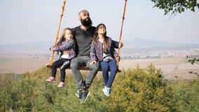 Tata chlanie z córkami na huśtawce pod drzewem zbiory wideo