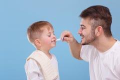 Tata czyści jego małych syna ` s zęby niebieska tła zdjęcie royalty free