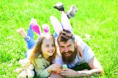 Tata i dziewczyna zakładamy Easter jajka w tradycyjnej łowieckiej grą wewnątrz Mężczyzna z brodą i śliczny dziecko kłaść na trawi fotografia royalty free