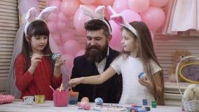 Tata i jego mała córka wpólnie zabawę podczas gdy przygotowywający dla Wielkanocnych wakacji Na stole jest kosz z wielkanocą zbiory