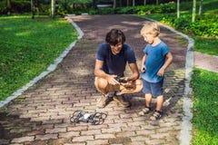 Tata i syn bawić się z trutniem, mężczyzna i chłopiec bawić się z lataniem, Zdjęcia Stock