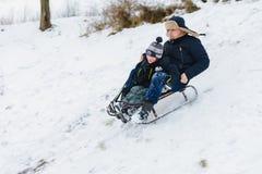 Tata i syn jedziemy jesteśmy zabawą w sledding, dziecko zdjęcie stock