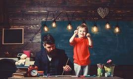 Tata obraz podczas gdy dzieciak bawić się Chłopiec pokazuje jego pięści stoi obok jego ruchliwie ojczulka Skoncentrowany ojciec i obrazy royalty free