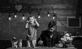 Tata obraz podczas gdy dzieciak bawić się Chłopiec pokazuje jego pięści stoi obok jego ruchliwie ojczulka Skoncentrowany ojciec i obraz royalty free