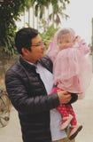 Tata patrzeje jej córki z szczęśliwym uśmiechem gdy jego dzieciak jest ubranym vell fotografia stock