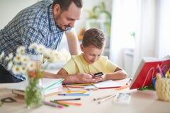 Tata pomaga jego syna robić pracie domowej domowy uczyć kogoś, domowe lekcje outside szkolne klasy z rodzicami ojciec egzamininuj zdjęcia stock