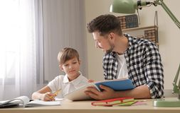 Tata pomaga jego syna z szkolnym przydzia?em obrazy royalty free