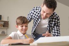 Tata pomaga jego syna z szkolnym przydzia?em obraz royalty free