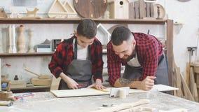 Tata pomaga jego syna zaznaczać w górę linii na drewnianej desce z władcą zdjęcie wideo