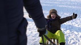 Tata stacza się jego syna na saniu Chłopiec ono uśmiecha się szczęśliwie Zimny słoneczny dzień swobodny ruch zbiory