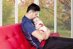 Tata trzyma jego męskiego dziecka na kanapie Zdjęcie Royalty Free