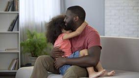 Tata trzyma jego małej córki delikatnie ściska ona na podołku, świadomy rodzicielstwo zdjęcie royalty free