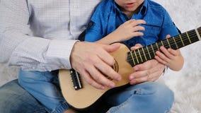 Tata uczy jego syna bawić się gitarę podczas gdy siedzący na ulowej leżance