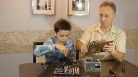 Tata uczy jego synowi nastolatka, jaki ` s wśrodku komputeru Płyta główna, procesor, źródło zasilania zbiory