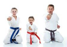 Tata z dwa córkami siedzi w obrządkowym poza karate i bije jego pięść Obrazy Royalty Free
