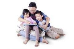 Tata z dwa dzieciakami czyta opowieść rezerwuje Fotografia Royalty Free