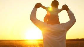 Tata znosi dziecka obsiadanie na jego ramionach przy zmierzchem złoty słońce zbiory wideo