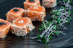 Tataki de color salmón japonés con sésamo y brotes de hierbas frescas En una placa negra de la arcilla Foto macra, fotos de archivo
