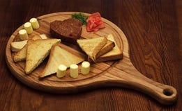 Tatar stek tjänade som i form av hjärta på runt träbräde Bröd, rostat bröd och smör runt om stek ombord Royaltyfria Bilder
