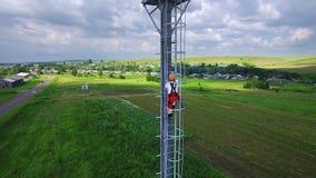 TATARSTAN, RUSLAND - ALMETEVO JULE, 2017: De luchtingenieursspecialist beklimt omhoog op de toren van de telecommunicatiecel voor stock video