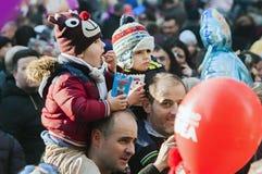 Tate porta i bambini sulle loro spalle in una via in pieno di peopl Fotografie Stock