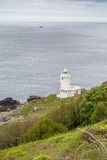 Tater du lighthouse in cornwall england uk. On the cliffs and against the back drop of the atlantic ocean Stock Image