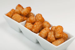 Tater Tots. Potato (tater tots) served on a white rectangular dish on a white background stock photos