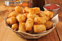 Tater tots. A basket of golden tater tots with beer in the background Royalty Free Stock Photo