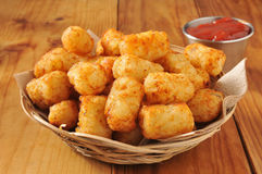 Tater tots and catsup. A basket of tater tots on a rustic wooden counter Royalty Free Stock Photo