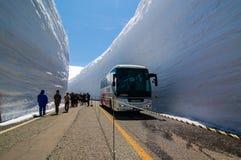 Tateyama Kurobe Alpine, tourists, trolley bus, Japan. Tateyama, Japan-April 19, 2014: The tourists walk along the road with high snow wall in bright blue sky on Stock Photo