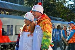 Tatiana Navka och Roman Kostomarov på den olympiska facklarelän Fotografering för Bildbyråer
