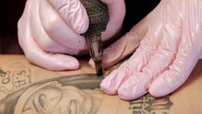 Tatoeeert de tatoegerings hoofd aantrekkelijke vrouw met dreadlocks cliënt aan het meisje op de heup Zwarte tatoegeringsmachine e stock footage